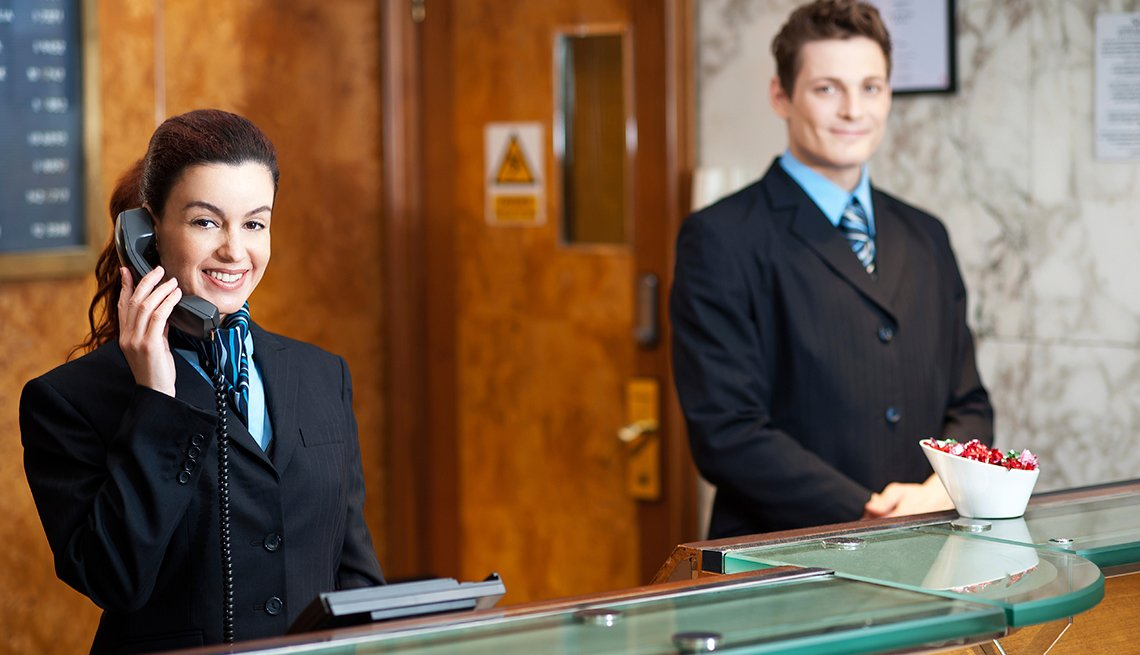 Hotel Employees at Reception Desk, Tips for Stretching Your Hotel Dollars