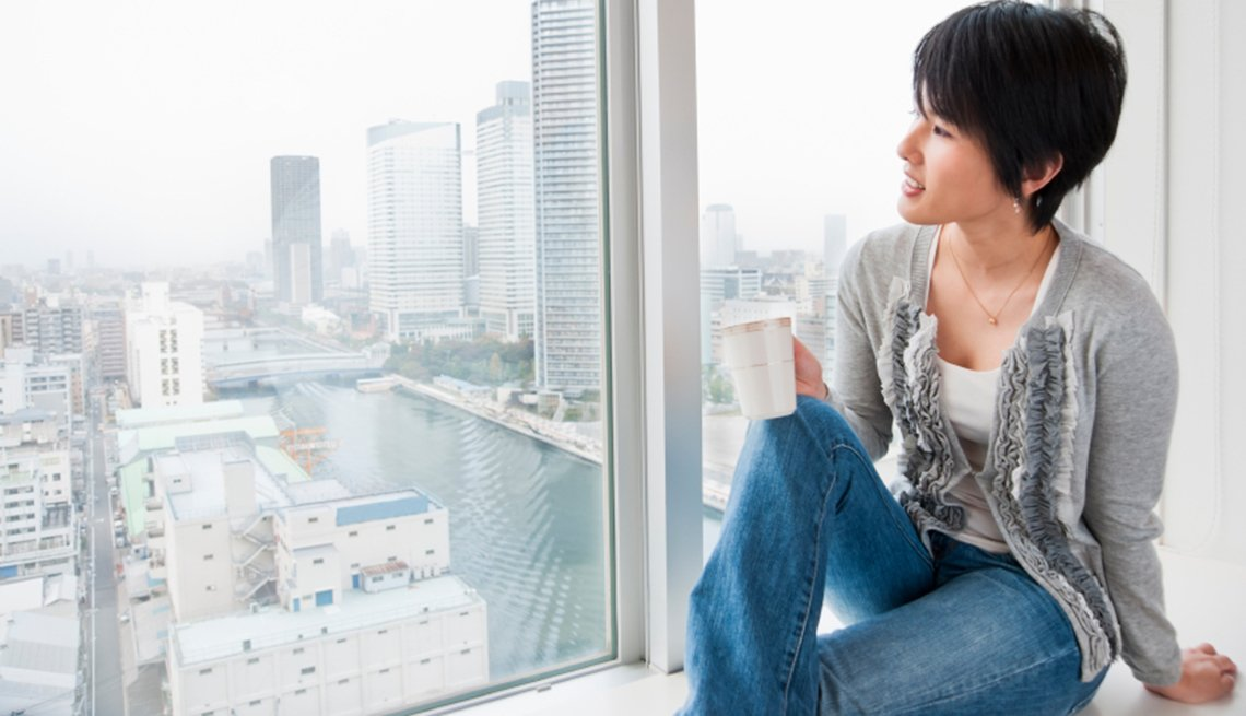Asian Woman with Cup Looks Out on Tokyo, How to Make the Most of the First Hours of Your Trip