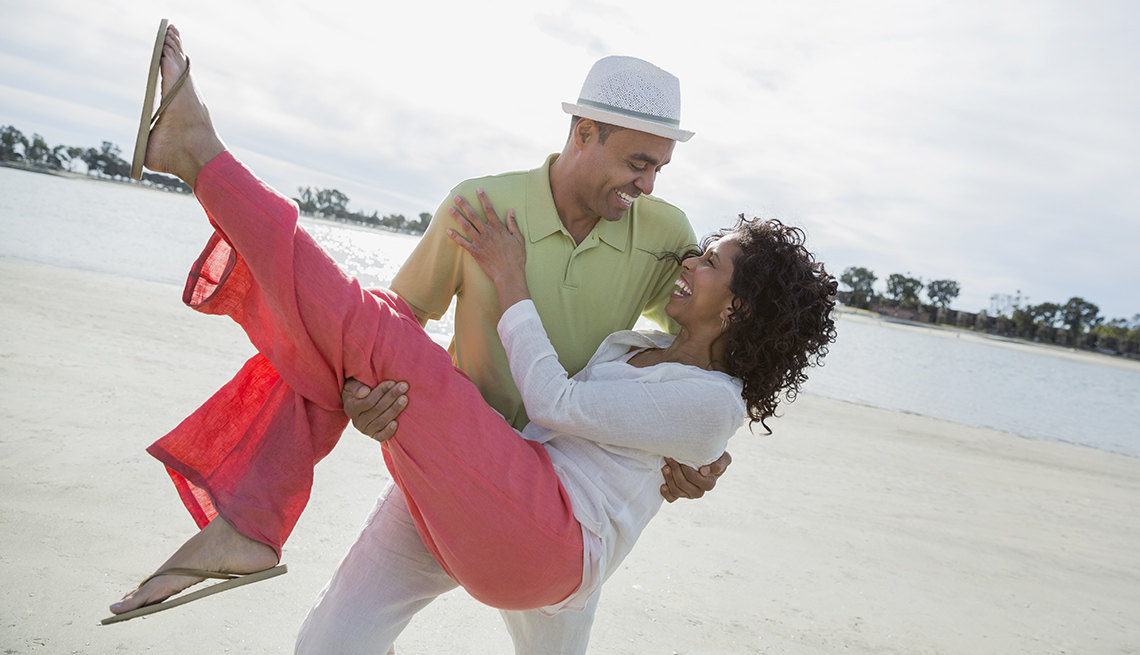 African American Man Holds And Tilts His African American Wife Back On The Beach, Unique Summer Vacation Ideas