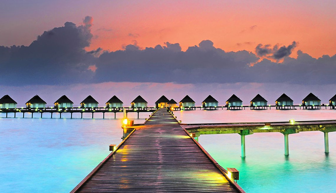Bungalow Huts Over The Water With Dock In Foreground In Maldives, Best Honeymoon Destinations