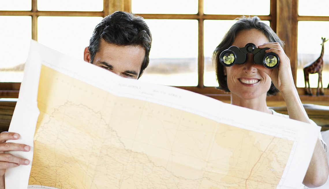 Caucasian Couple In Bed, Man Looking At Map, Woman Using Binoculars, Tips For Transforming Obligation Trips Into Vacations