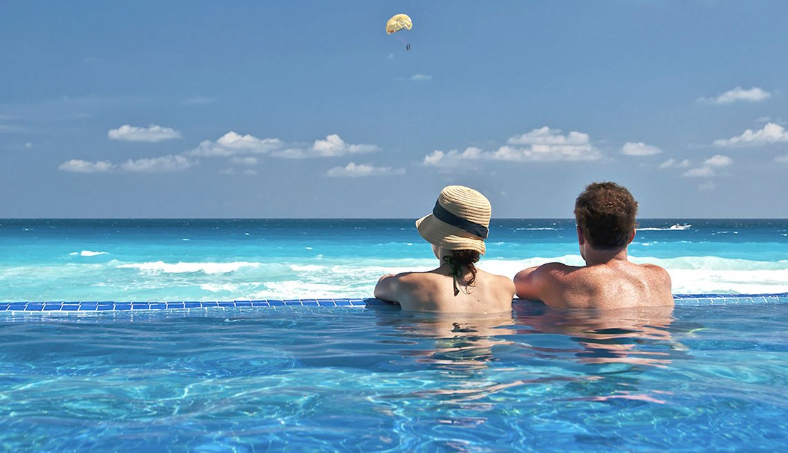 Couple Lounges In An Infinity Pool Overlooking The Ocean At Resort In Caribbean, Best Honeymoon Destinations