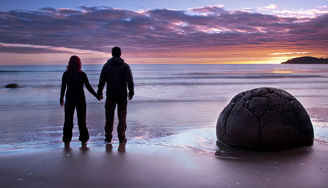 Couple Holds Hands On Beach Looking At Sunset In New Zealand, Best Honeymoon Destinations