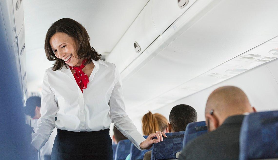 Female Flight Attendant Walks Down Aisle In Plane, Airline Freebies