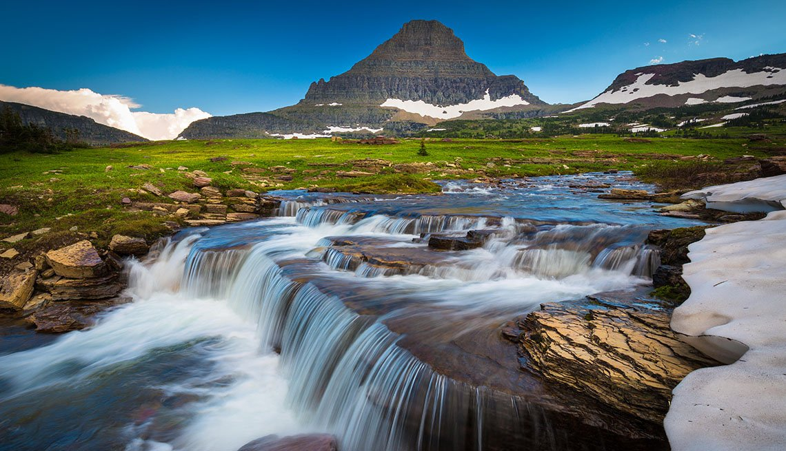 View Of Stream Over Rocks With Mountain In Background In Glacier National Park Near USA Canada Border, Visit Natural Wonders