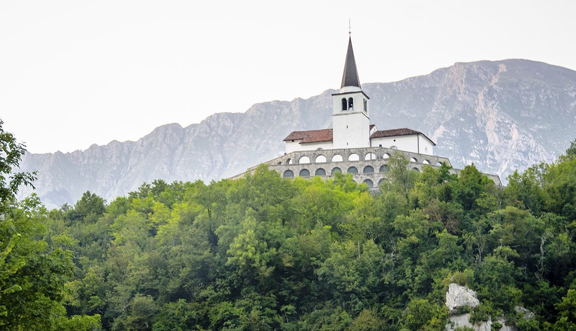 A Church Steeple Peeps Above The Tree Line In Kobarid Slovenia, Under The Radar Destinations