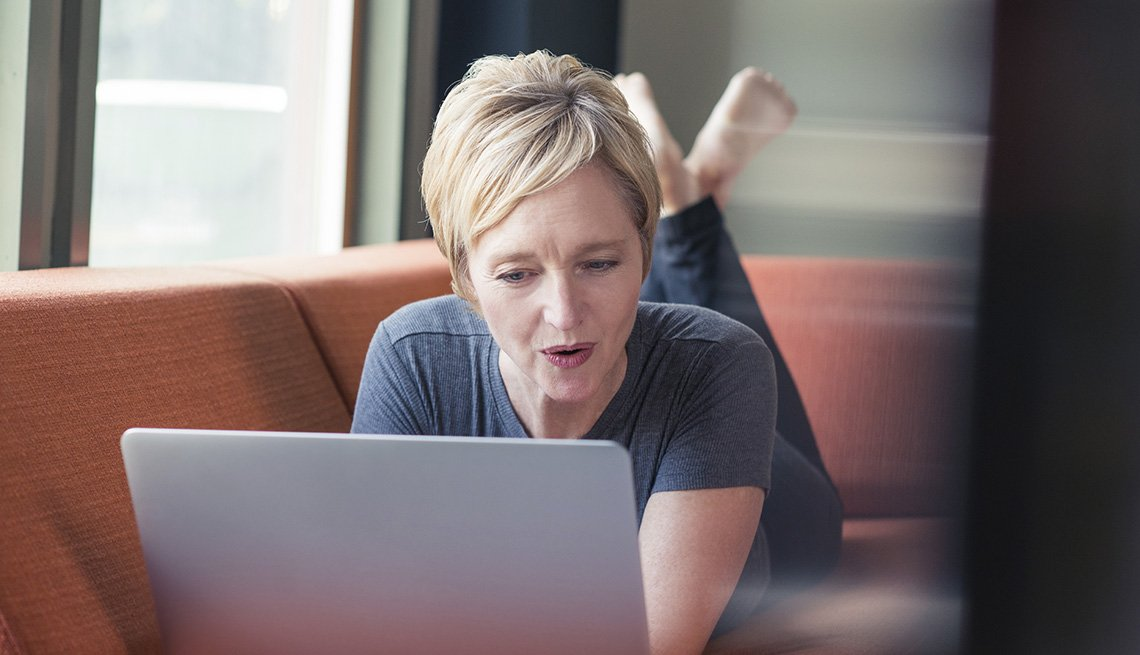 Woman Lies On A Sofa While Doing Research On Her Laptop Computer, Save On Solo Travel