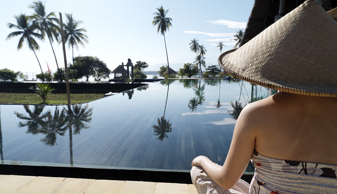 Woman Sits In Traditional Hat Overlooking The View In Lombok Island In Indonesia, Under The Radar Destinations
