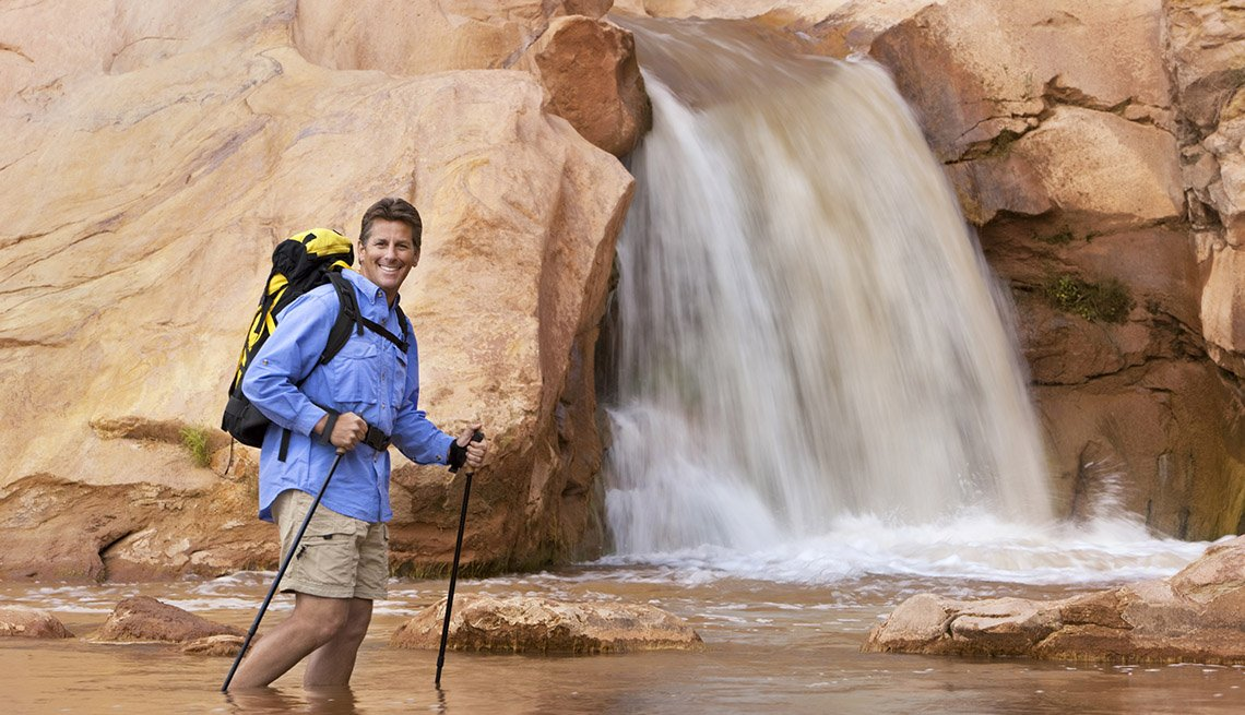 Man Stands In Water While Hiking With Small Waterfall Behind Him, Save On Solo Travel