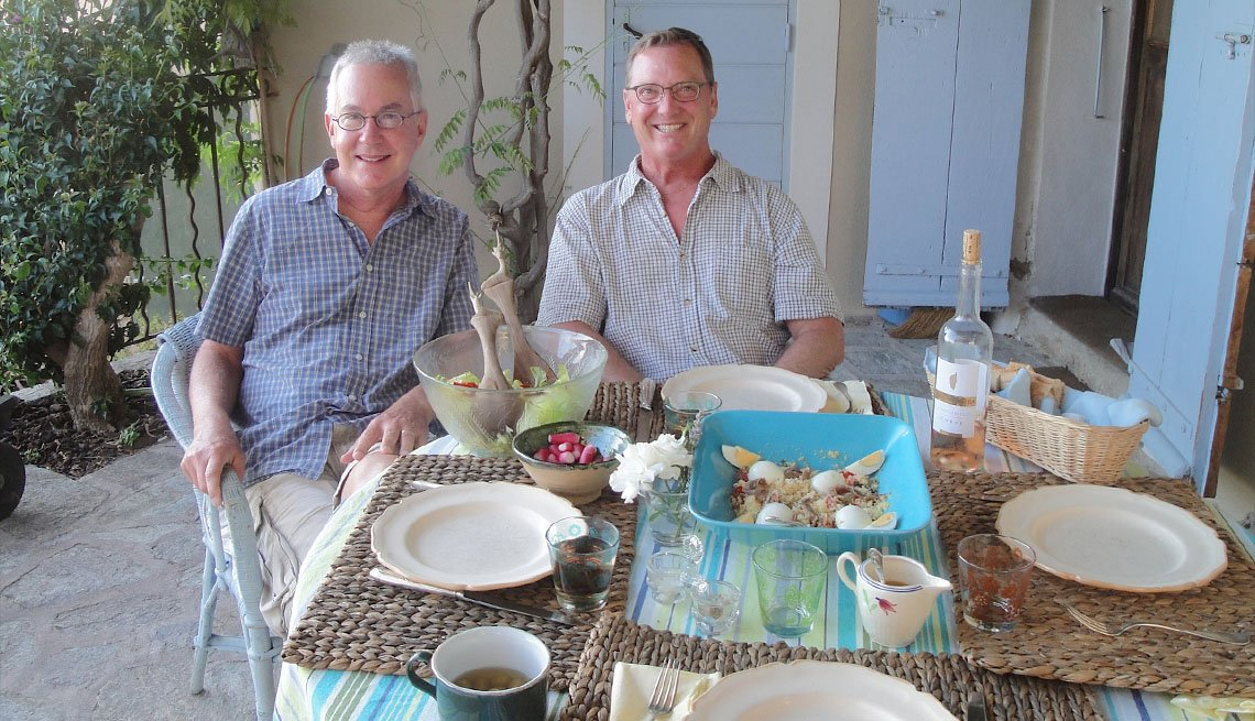 Two Men Enjoy A Meal On The Outdoor Patio, House Swapping Tips