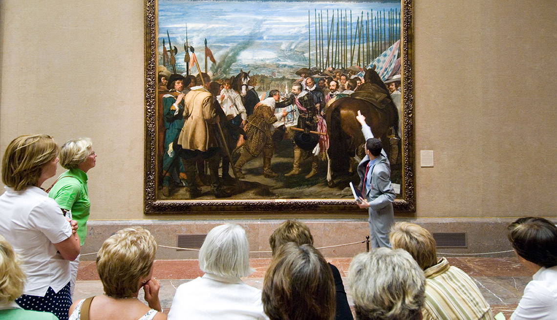 A Group On A Tour In A Museum Listen Intently To Museum Guide While Looking At Painting, Travel Insider Guide To Museums