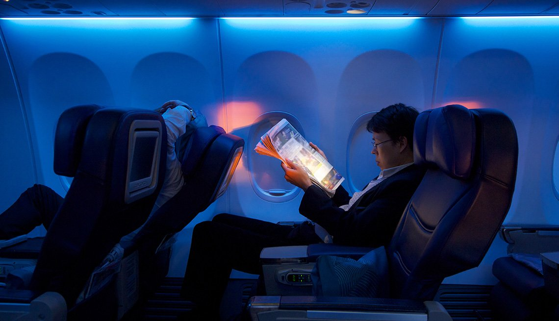 Passenger Reads Magazine In Airplane At Night, Airline Freebies