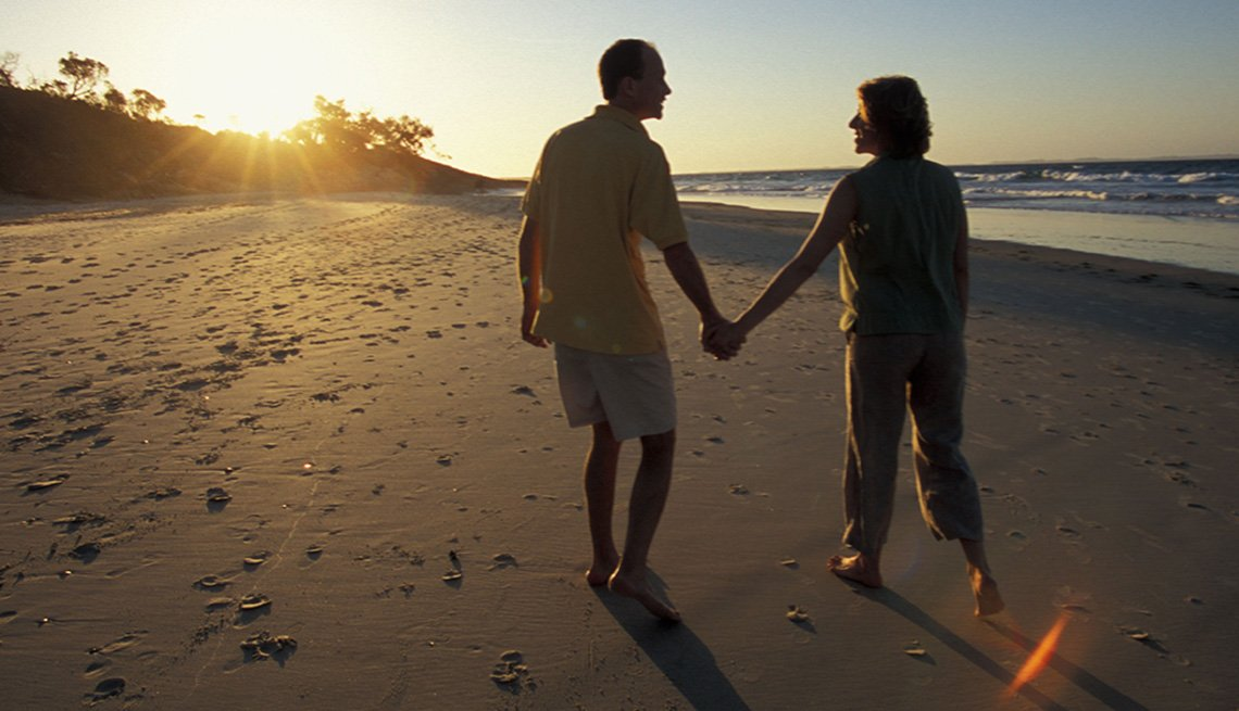 A Couple Holds Hands And Walks On The Beach At Sunset In North Stradbroke Island In Queensland Australia, Under The Radar Destinations
