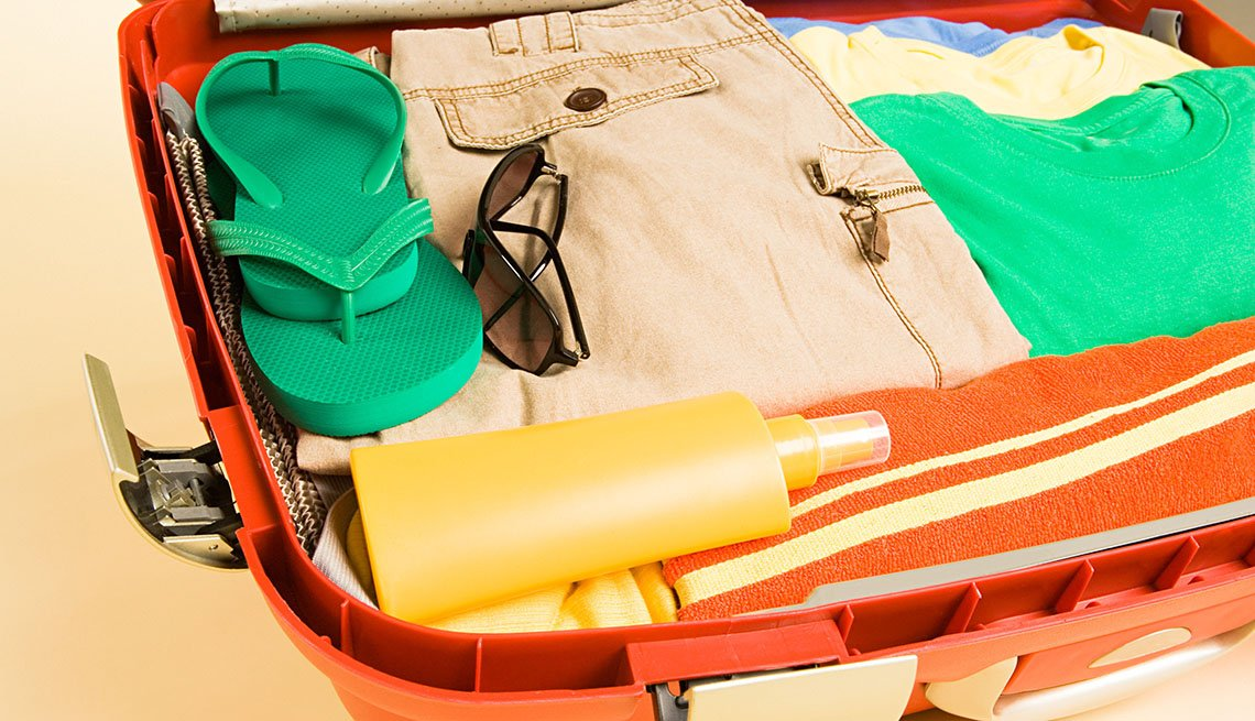Open Travel Suitcase With Clothes And Spray Bottle Inside, Travel Mistakes To Avoid