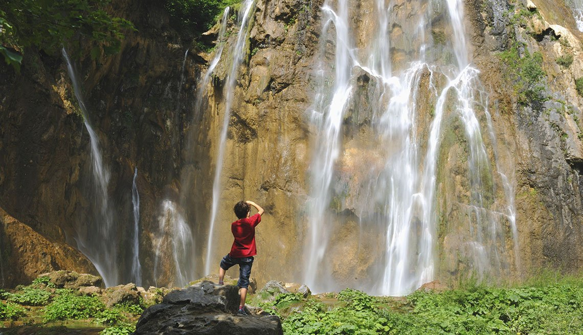 Woman Takes A Photo Of The Waterfall In Plitvice Lakes National Park In Croatia, Under The Radar Destinations