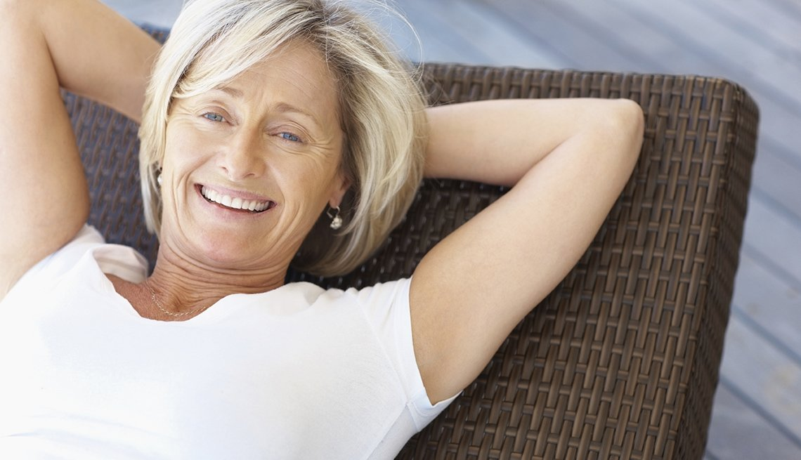 Smiling Middle-Aged Caucasian Woman Reclining In Her Chair, Save On Solo Travel