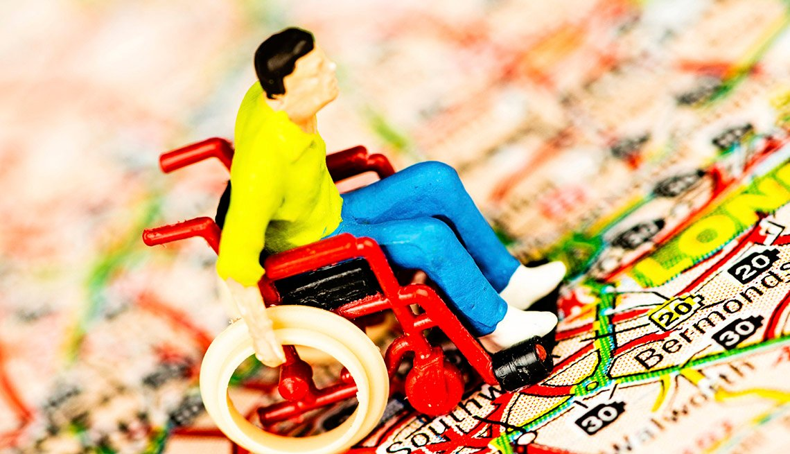 Toy Of Man In Wheelchair Sitting On Map, Travel Tips For Mobility Challenged