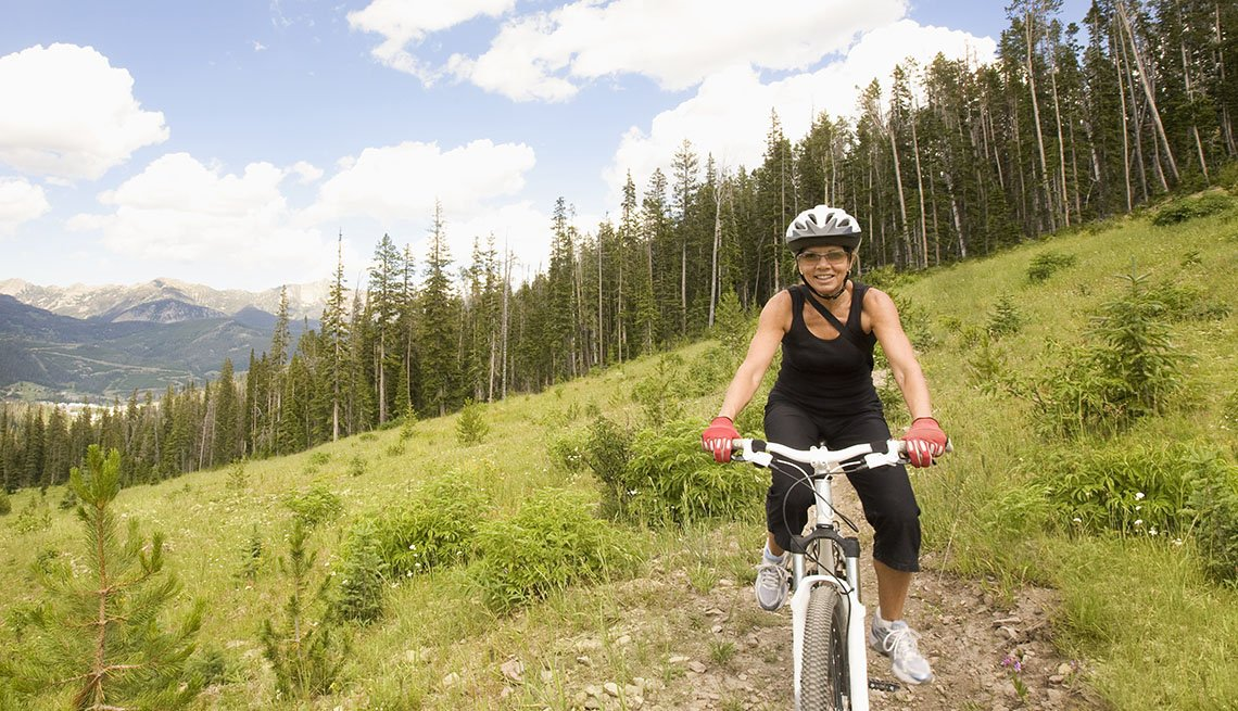 Woman On A Mountain Bike With The Mountain Range Behind Her, Unique Summer Vacation Ideas