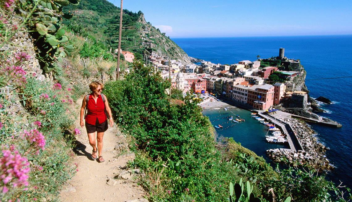 Woman Walks On Narrow Side Of Mountain Cliffside By Ocean Resort, Unique Summer Vacation Ideas