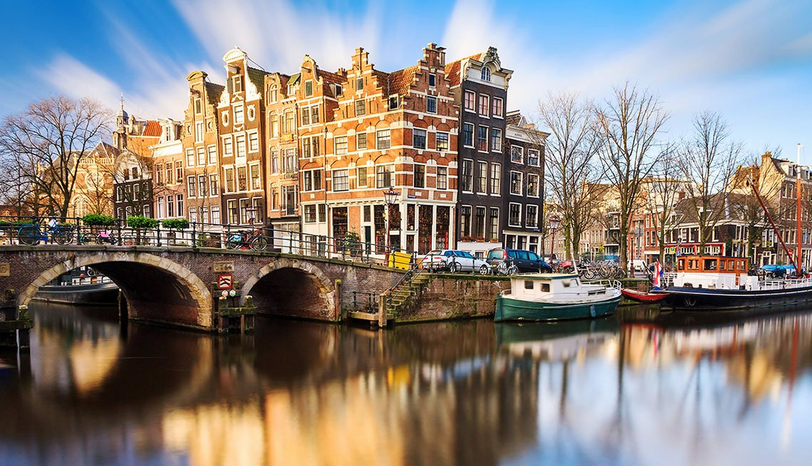 View Of The Canal, Boats, Bridge And Buildings Of Amsterdam Netherlands, New Year's Eve Destinations