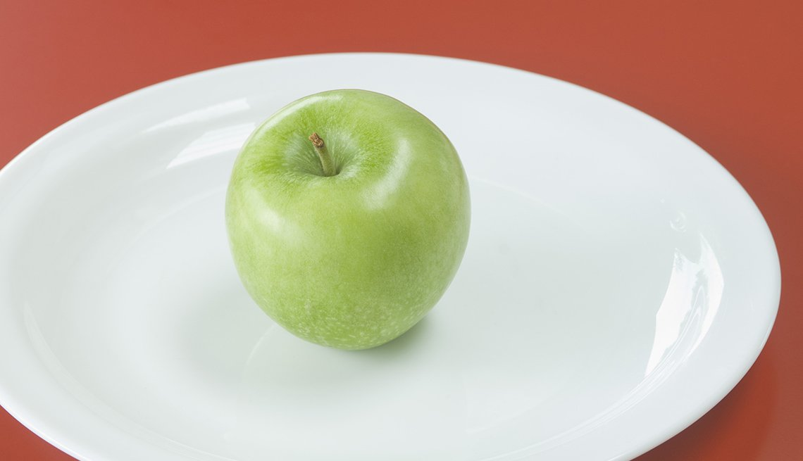 A Green Apple On A White Porcelain Plate, Foods To Avoid Before Flying
