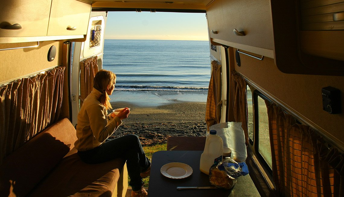 Woman Enjoys The View From The Back Door That Opens To The Beach View From Her RV, Tips From Experienced RV Travelers