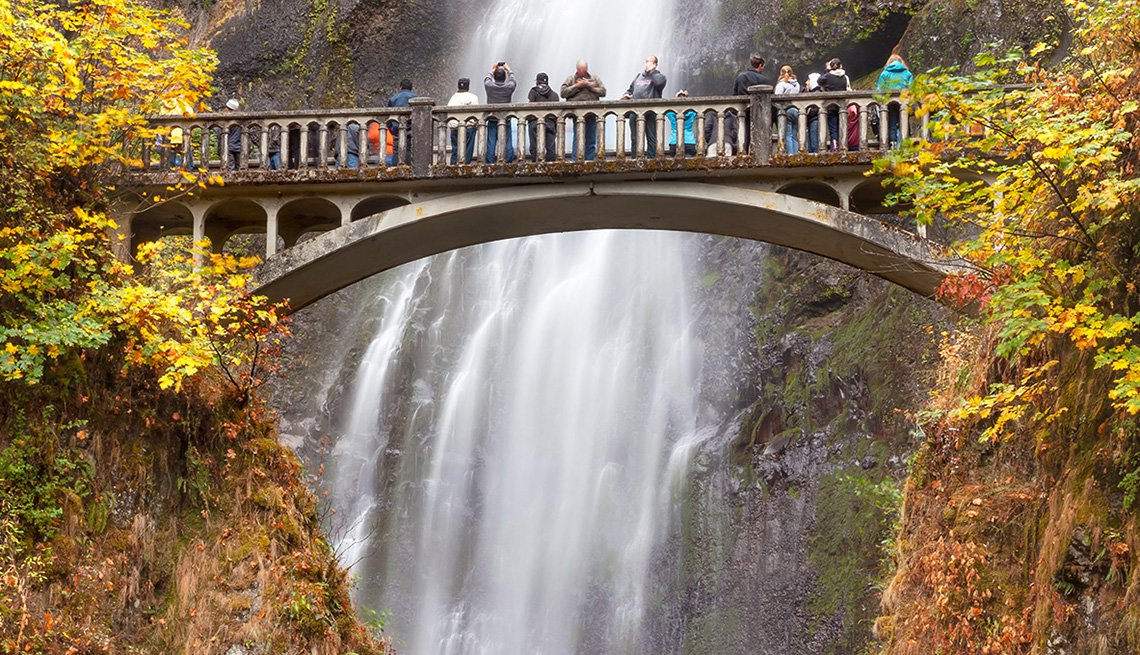 Tourists Watch The Waterfall From The Bridge In The Columbia River Gorge In Oregon, Best Fall Foliage Spots In America