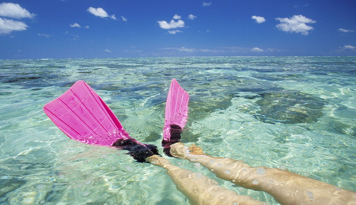 Woman With Pink Flippers Floats In The Ocean, Unique Vacation Ideas