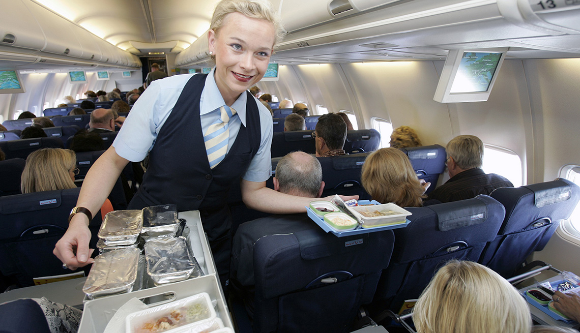 A Young Female Flight Attendant Hands Out Food Trays On Plane