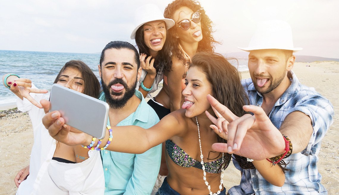 A Group Takes A Selfie On Beach, AARP Traveler's Tips