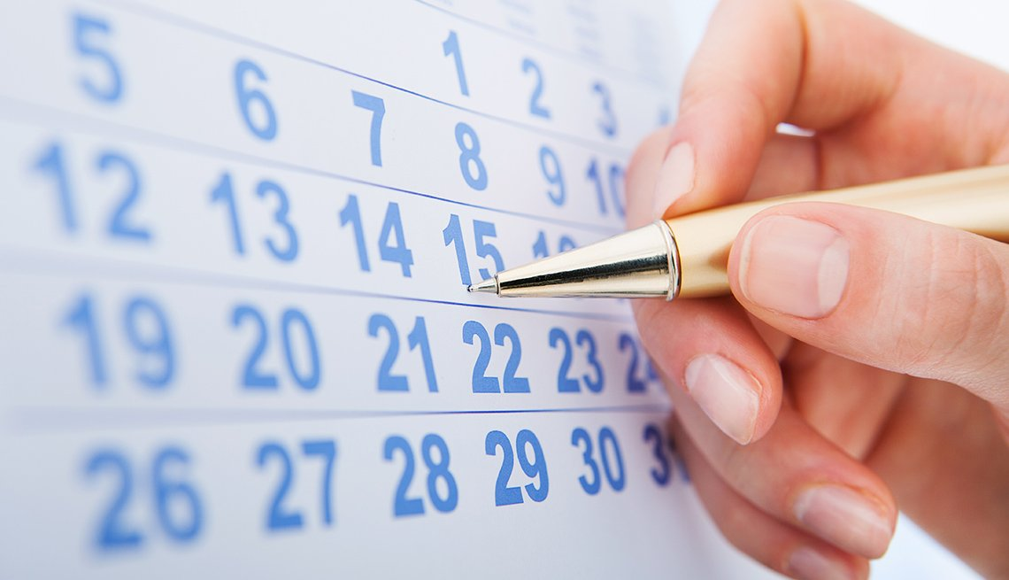 Close Up Of A Woman's Hands Holding Pen Over A Calendar, Cruise Ship Guide And Tips