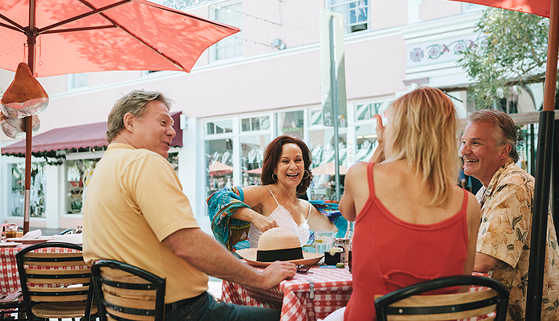 Middled Aged Caucasian Couples Enjoy Meal Together At Outdoor Cafe, Freebird Club AirBnB For Seniors