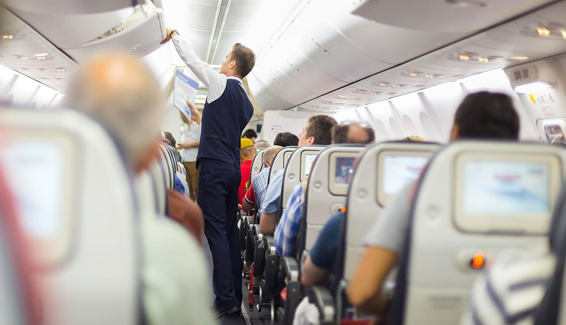 Flight Attendant with Passengers on Airplane, Should You Pay More to Fly, Travel