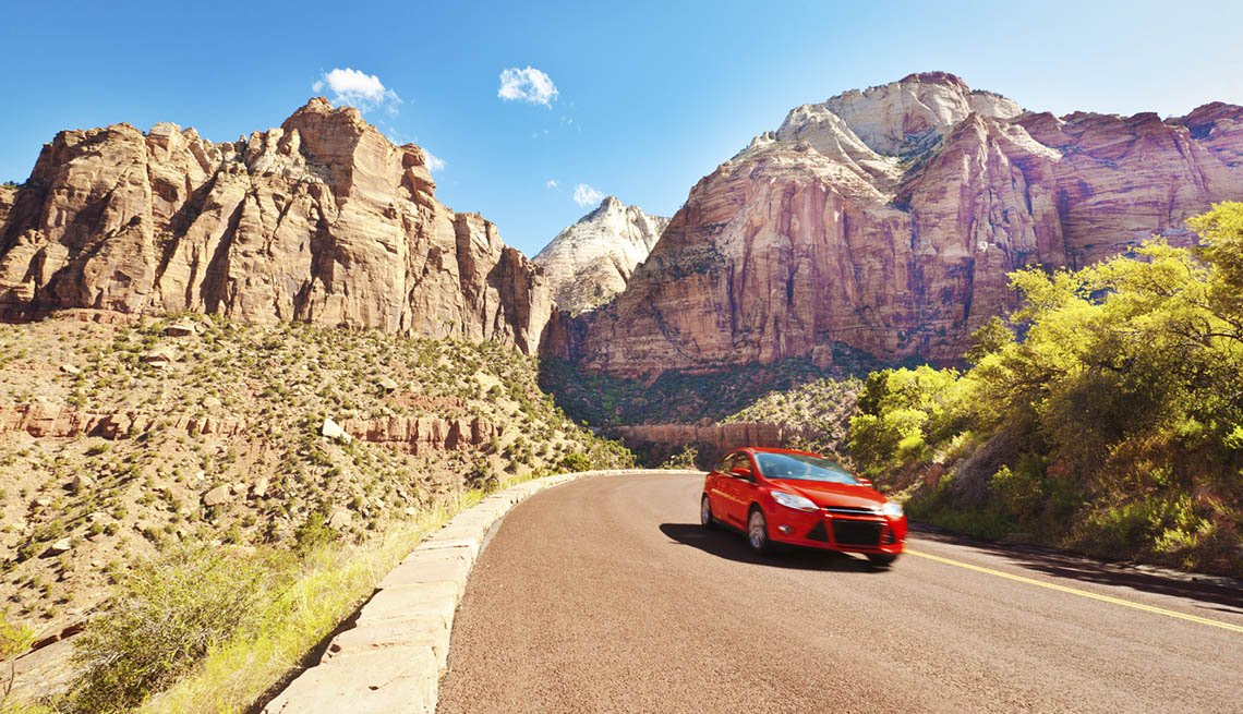 A Red Sports Car On Road Through Mountains, AARP Traveler's Tips