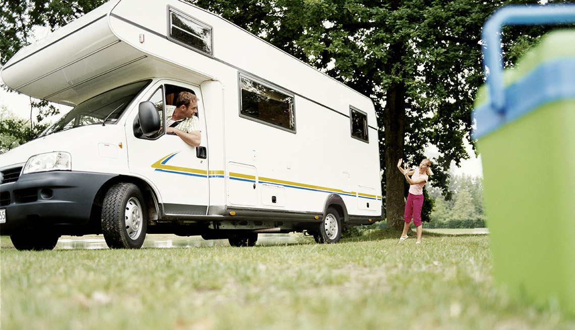 A Man Practices Backing Up In Lot With His Wife Assisting Him Outside RV, Tips From Experienced RV Travelers
