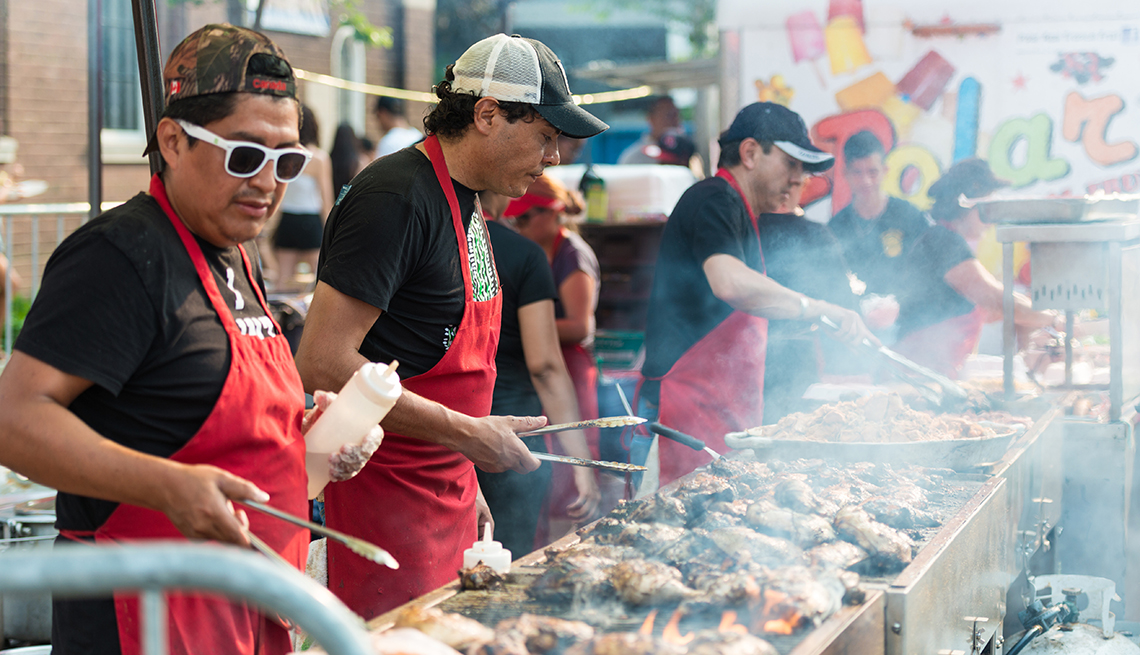 A Line Of Men Tend To The Grill During Street Festival, Best Latin Festivals In America