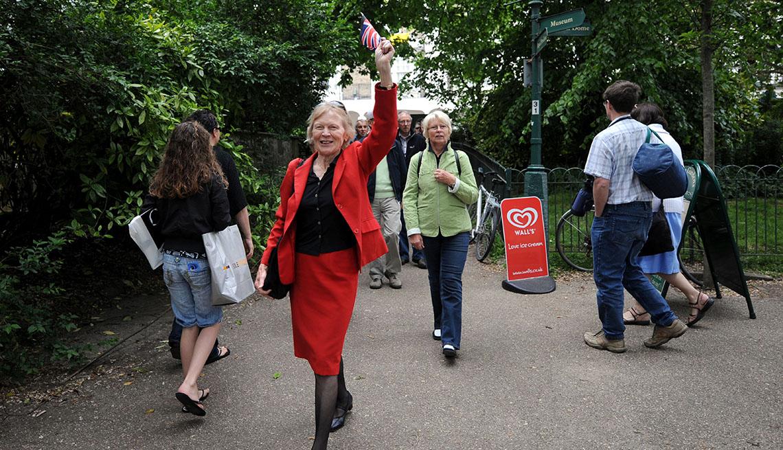 Elderly Woman Leads Her Tour Group Through A Park, Unique Vacation Ideas