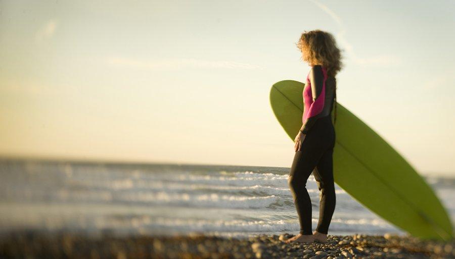 A Lone Surfer Girl On Rocky Beach Girlfriend Getaways