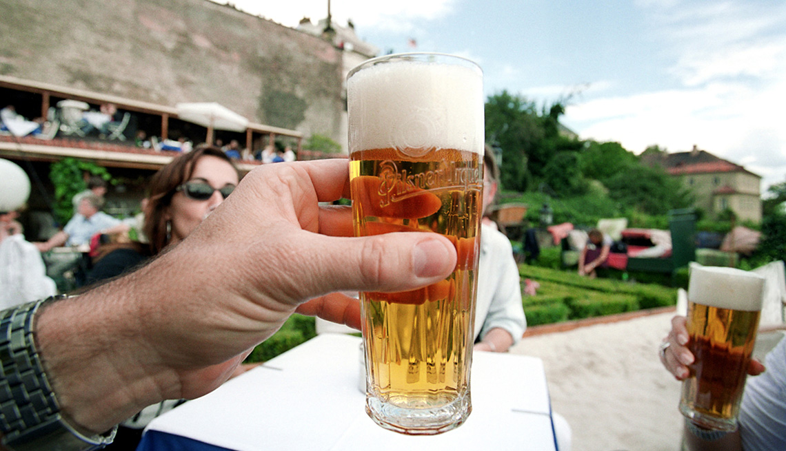 Man Holds Beer Glass And Toasts His Companions At Outdoor Cafe, How To Choose A Guided Tour
