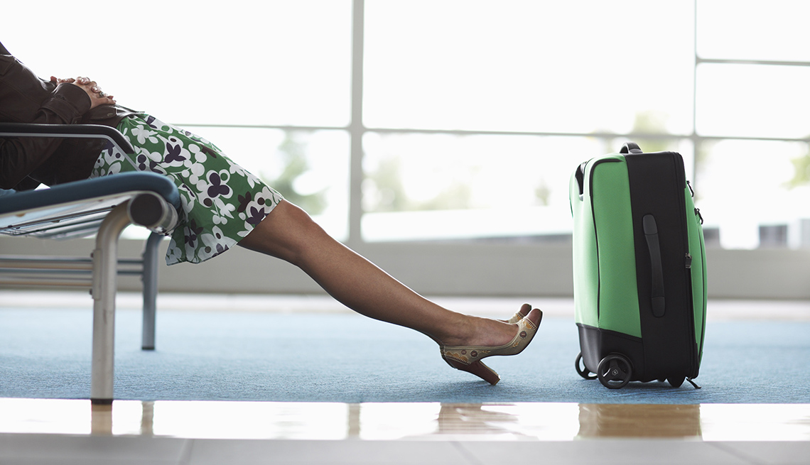 A Woman's Legs As She Sits In The Airport Terminal With Her Luggage, What To Do When Your Flight Is Cancelled