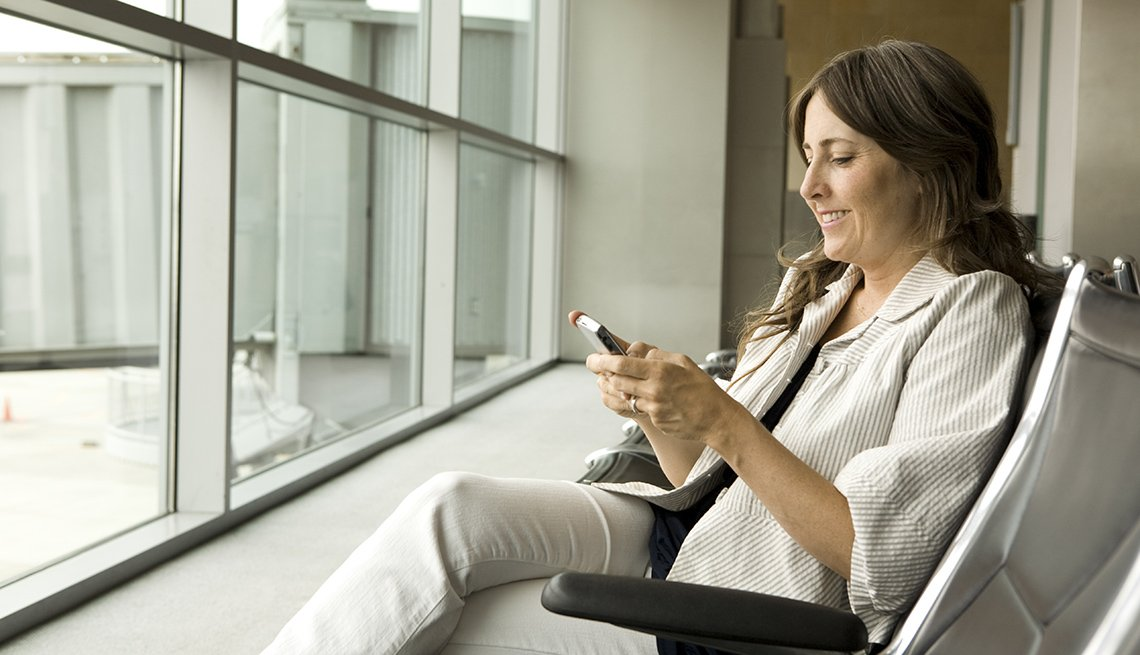 Caucasian Woman Sits In Airport Gate Looking At Her Cellphone, Best Travel Apps