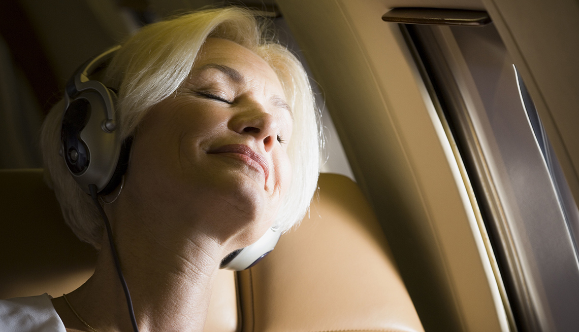 Woman Asleep On Plane With Headphones On