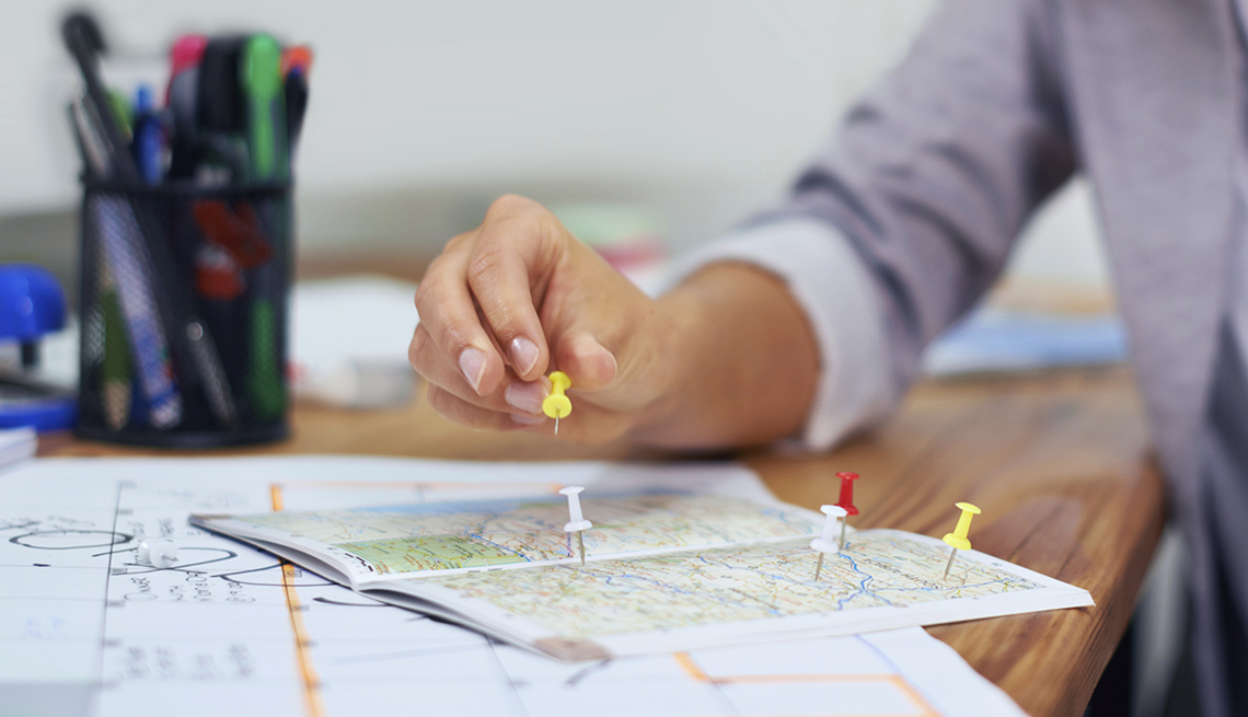 Close Up Of A Woman's Hand Placing Push Pins In A Map, What Travel Agents Can Do For You?