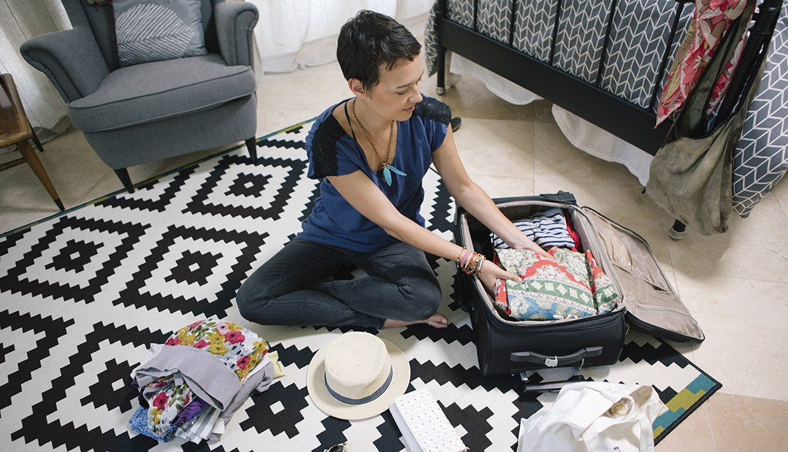 Caucasian Woman Sits On Floor Of Her Home Packing Her Luggage For Trip, How To Stay Healthy Abroad