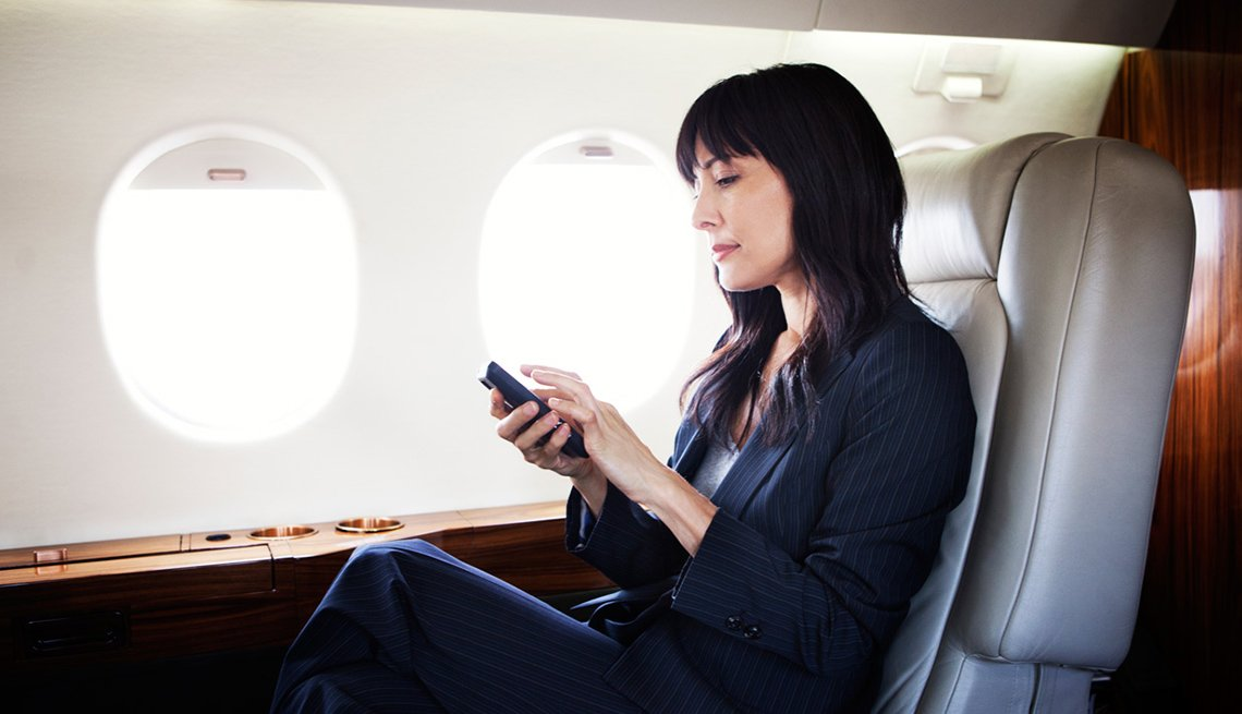 Business Woman On Plane Looks At Her Cell Phone, Samantha Brown's Favorite Travel Apps