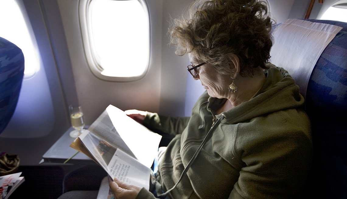 Elderly Woman Sits On Plane With Her Reading Material, Must Have Carry On Items