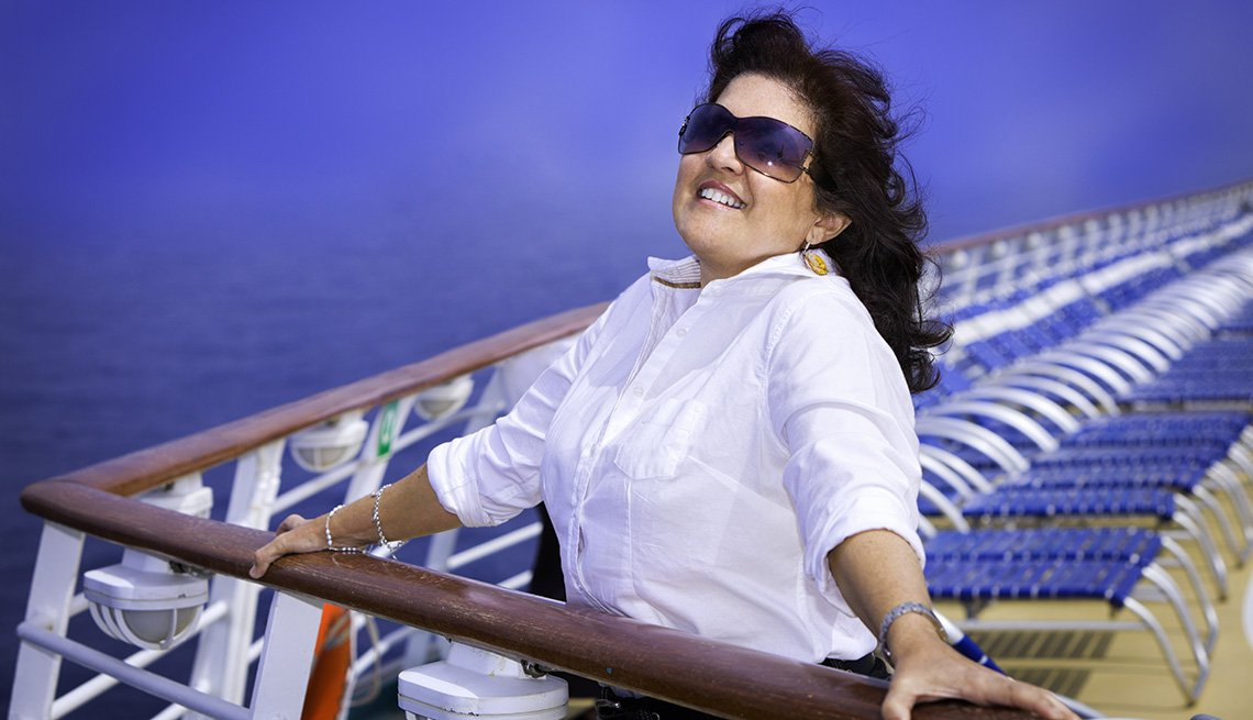 Smiling Caucasian Woman Holds Onto Railing On Ships Deck, Cruise Ship Myths