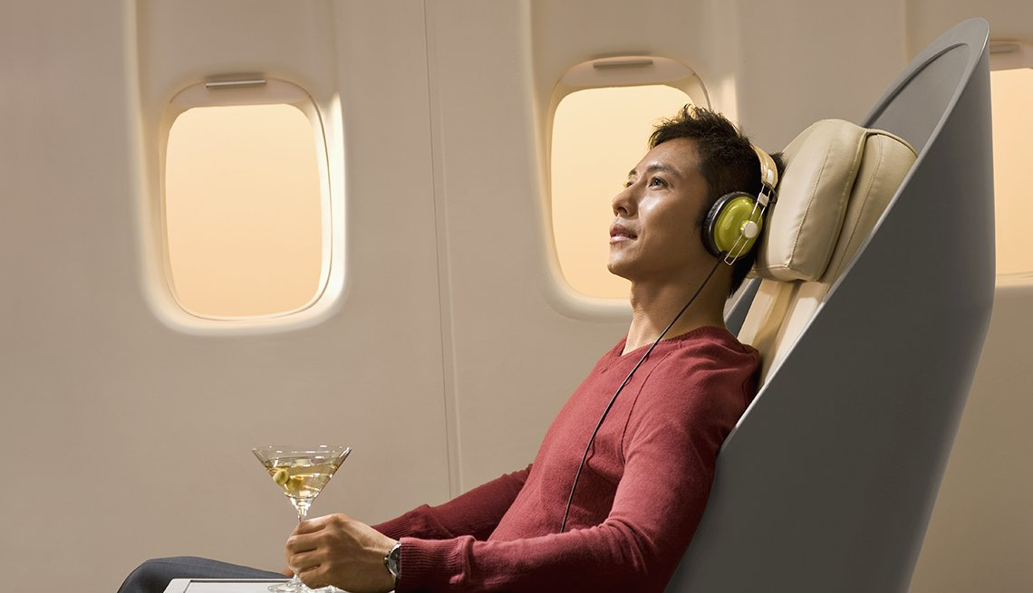 Asian Man Sits On Plane With Cocktail And Headphones On, Gifts For Travelers