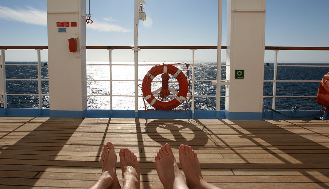 Couple's Feet While They Lounge On Deck Chairs On Cruise Ship Deck, Travel Trends