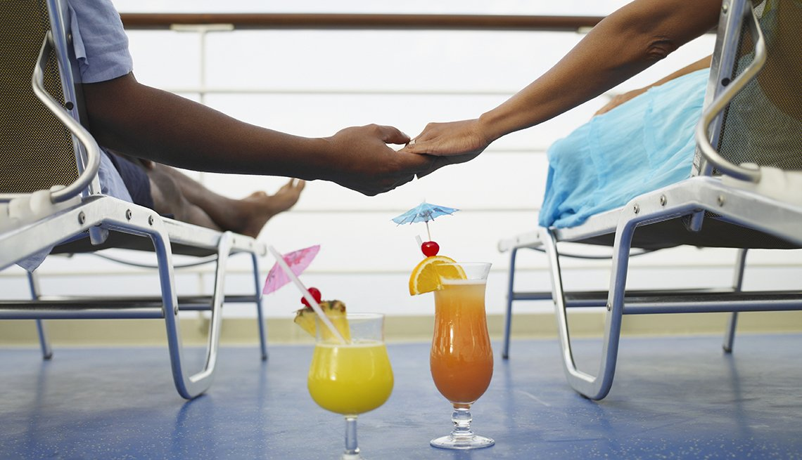 Couple Holds Hands While Sitting On Deck Chairs On Cruise Deck With Cocktails, Theme Cruises